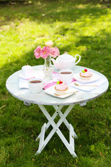 Coffee table with teacups and tasty cakes in garden
