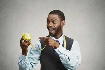 Happy smiling man advising on healthy diet, holding green apple