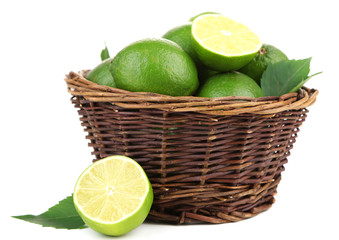 Fresh juicy limes in wicker basket, isolated on white