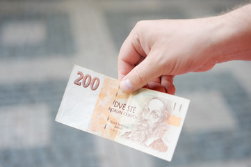 Man holding paper money (czech koruna)