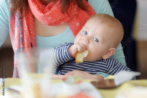 Baby boy having piece of bread - 67896210