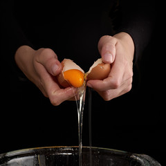 Hands breaking an egg.