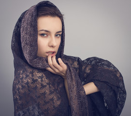 Portrait of a beautiful young woman in a black lace shawl.