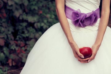 Bride's hands holding red apple - symbol of love