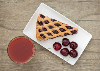 Fresh backed cherry pie and juice on wooden table