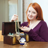 teenager girl looks jewelry in treasure chest at home