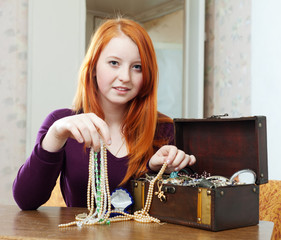 teen girl chooses jewelry in treasure chest
