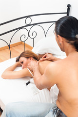Black-haired man massaging his wife