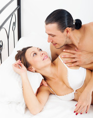 Loving awaking couple in bed
