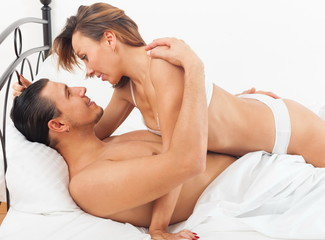 Ordinary lovers kissing in bed