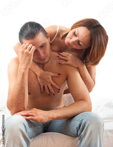 Woman consoling the depressed husband in bed
