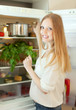 Positive woman looking for something in refrigerator