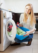 Happy woman loading clothes into  washing machin