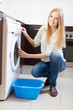 long-haired huosewife  with washing machine at home