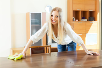 Cheerful  woman cleaning table at home