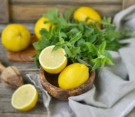 ripe organic lemons in a and fresh mint on a wooden background