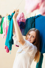 Long-haired housewife drying clothes