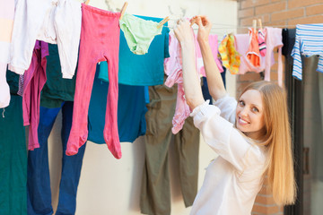 Positive long-haired girl drying clothes on clothes-line