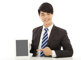 smiling young business man show a tablet