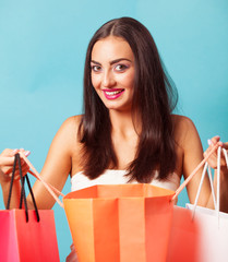 Brunette girl with shopping bags on blue backgorund.