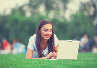 Brunette girl with notebook on green grass in the park.