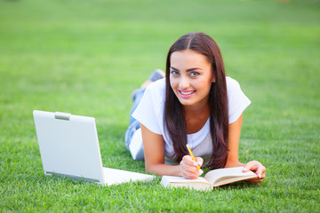 Brunette girl with notebook and book on green grass in the park.