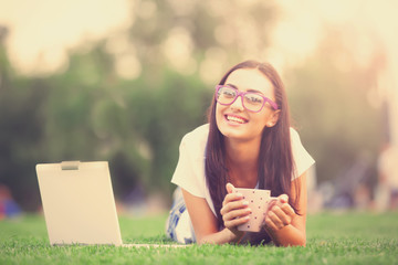 Redhead girl with notebook and cup of coffee on the green grass.