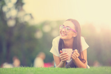 Brunette girl with cup of coffee on green grass in the park.