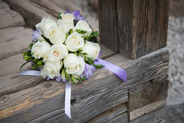 Wedding bouquet with white roses on wood background