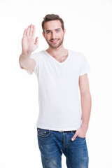 Young happy man requiring stop with his hand.