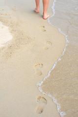 Women's legs beach footprnts