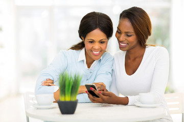 african mother and daughter using smart phone