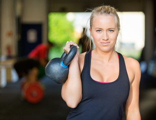Confident Female Athlete Lifting Kettlebell