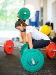 Fit Woman Picking Barbell At Healthclub