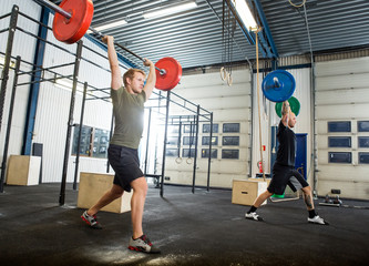 Athletes Exercising With Barbells