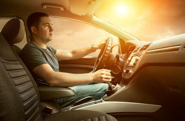 Man sitting and driving in the car under sunset sky