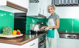 Smile woman cook or housewife holding pan