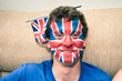 Funny man with British flag painted on face