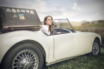 beautiful woman who is driving a vintage car