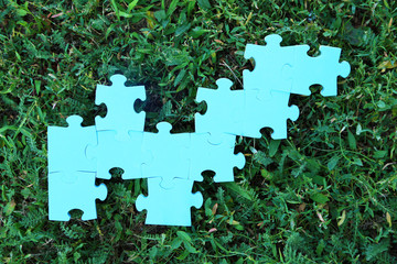 Puzzle pieces on green grass background. Green space concept