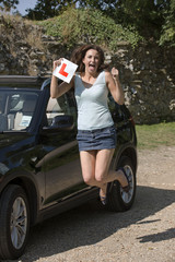 Jubilant driver with L plate after passing her driving tes