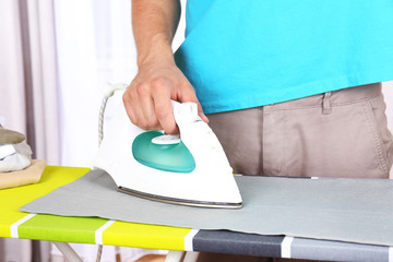 Young man ironing clothes in room