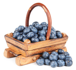 Delicious blueberries in wooden basket isolated on white