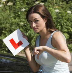Woman driver holding L plate & thumbs down failure on test