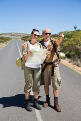 Hiking couple looking at map on the road and pointing ahead