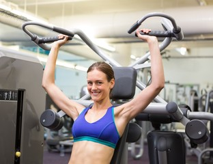 Fit happy brunette using weights machine for arms