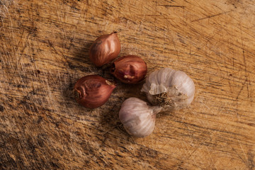 fresh Onions and garlic on a wooden background.