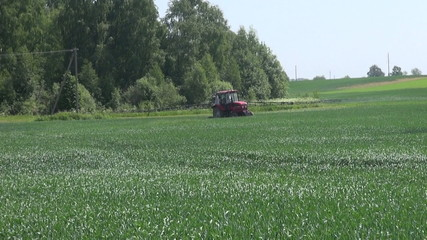 Tractor spraying field with herbicides and fertilizer