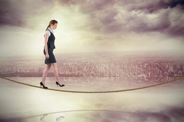 Composite image of redhead businesswoman stepping on tightrope