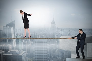 Young businessman pulling a tightrope for business woman